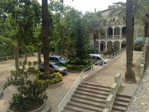 Cotxes aparcats a Can Solei, entre els dos edificis on abans havia l'escola.