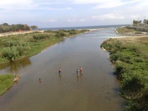 Gent pescant i banyant-se a la desembocadura del riu Besòs