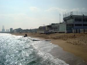 Foto de la platja dels Patins a Vela on es veu el col·lector que queda descobert a mitja platja.