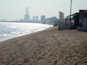 Fotografia de la platja on es veu com les onades arriben a tocar els edificis