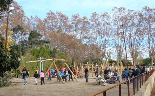 Un munt de gent a l'espai de jocs, nens i adults acompanyant-los
